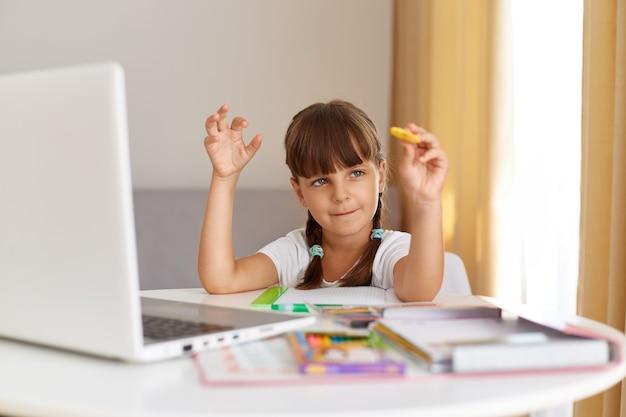 Colegiala linda de pelo oscuro con camiseta blanca posando interior en casa, sentado en la mesa rodeada de libros, frente a la computadora portátil, educación en línea.