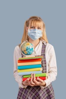 La colegiala con una máscara médica protectora tiene una pila de libros y un globo terráqueo sobre un fondo gris.