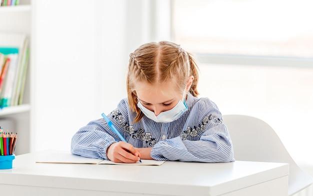 Colegiala en máscara protectora escribiendo con lápiz en el cuaderno sentado en el pupitre de la escuela