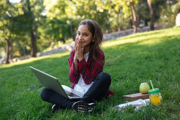 Colegiala morena contenta sentada en el césped con la computadora portátil