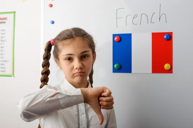 Colegiala mostrando los pulgares hacia abajo en el clcassroom con una bandera francesa en el tablero