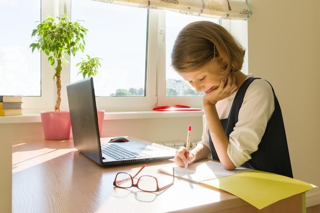 Colegiala, niña de 8 años, sentada a la mesa