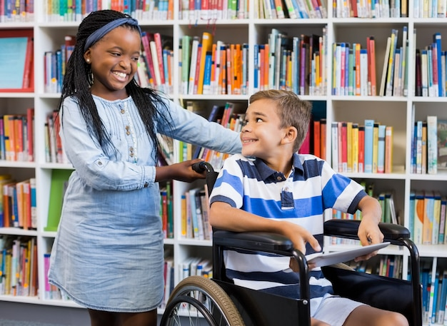 Colegiala de pie con niño discapacitado en silla de ruedas