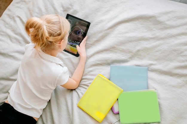 Colegiala preadolescente haciendo sus deberes con tableta digital en casa. niño usando gadgets para estudiar. educación y aprendizaje a distancia para niños. educación en el hogar durante la cuarentena. quédate en el entretenimiento en casa.