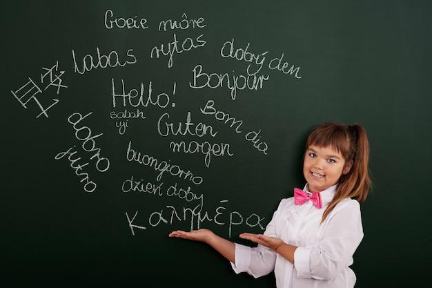 Colegiala presentando frases extranjeras en la pizarra