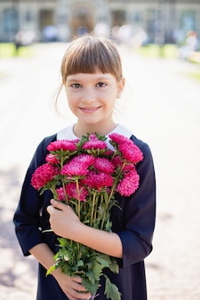 Colegiala con ramo de flores en uniforme escolar