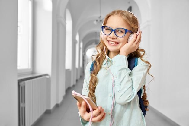 Colegiala rubia feliz escuchando música de auriculares