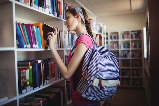 Colegiala seleccionando libro en biblioteca