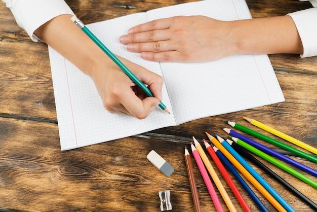 La colegiala se sienta en su escritorio y dibuja en un cuaderno con lápices de colores.