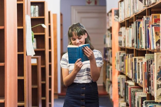 Colegiala sonriente leyendo un libro en la biblioteca