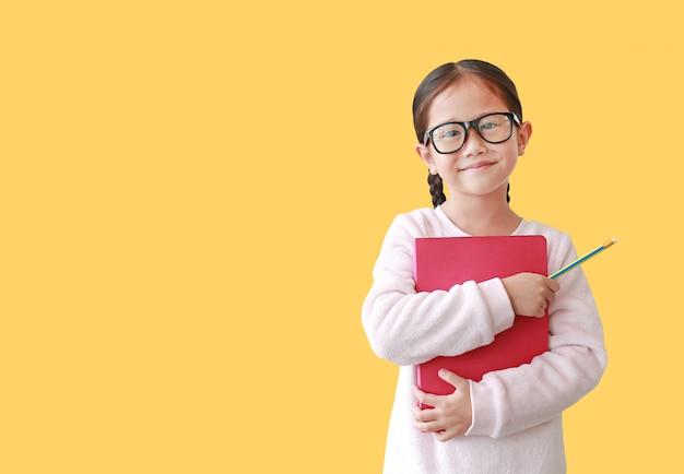La colegiala sonriente que lleva la lente abraza un libro y sostener el lápiz disponible aislado sobre amarillo.