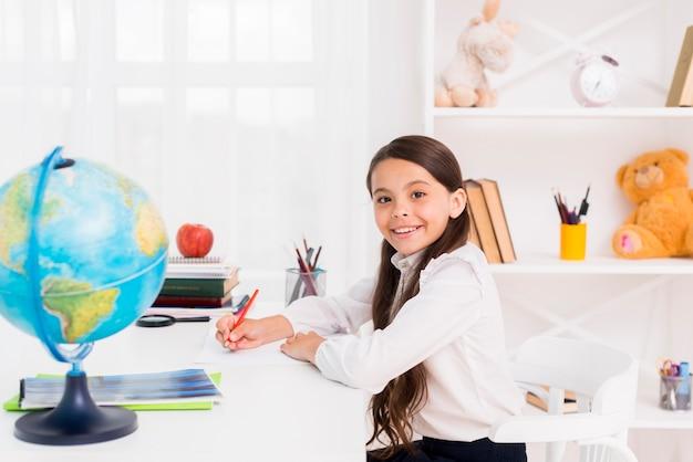 Colegiala sonriente en uniforme estudiando en casa
