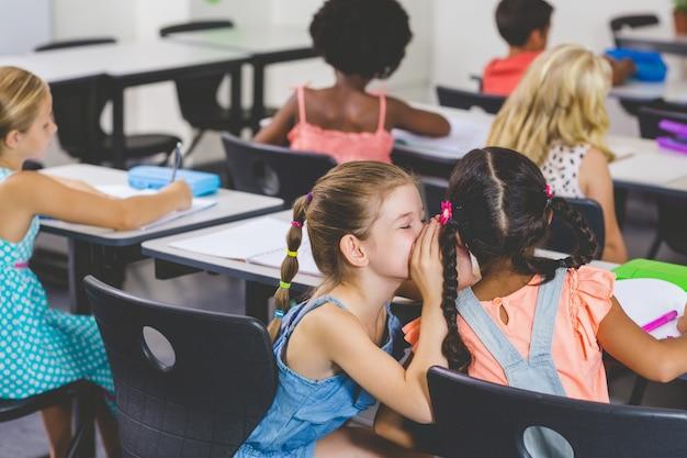 Colegiala susurrando al oído de su amiga en el aula