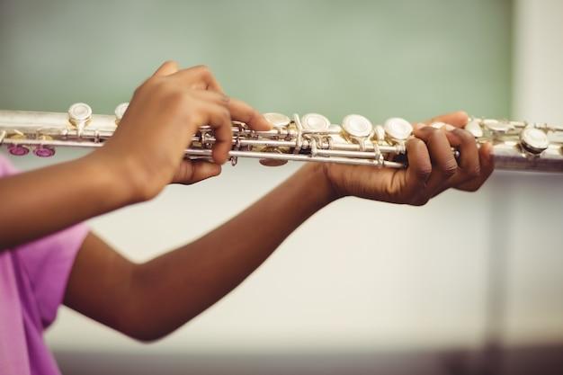 Colegiala tocando la flauta en el aula