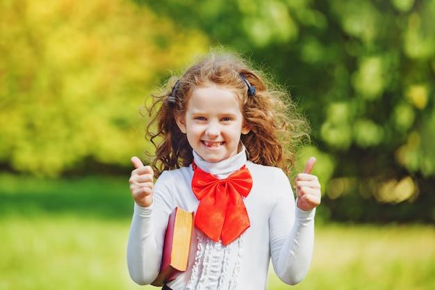Colegiala en el uniforme escolar que muestra los pulgares para arriba en el parque.