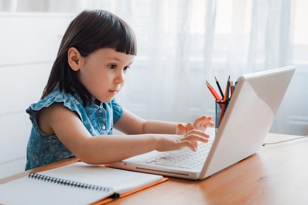 Colegiala usando laptop en casa