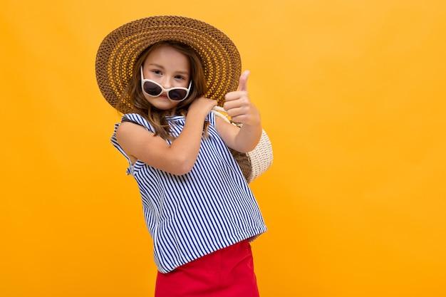 Colegiala va de viaje, foto de una niña en un sombrero de playa sobre un fondo amarillo