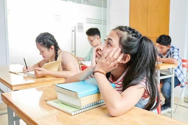 Colegiala vietnamita sentada en su escritorio con pila de libros y soñando en lugar de estudiar en la lección de inglés