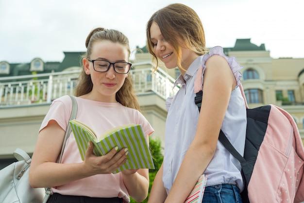 Colegialas adolescentes con mochilas escolares libros.