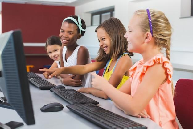 Colegialas usando la computadora en el aula