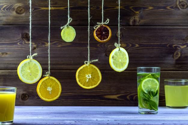 Colgando de hilos rodajas de limón, naranja y lima
