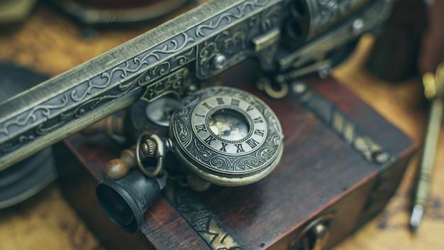 Colgante antiguo de pistola y reloj