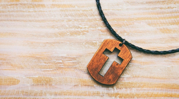 El colgante en forma de cruz en el escritorio de madera.