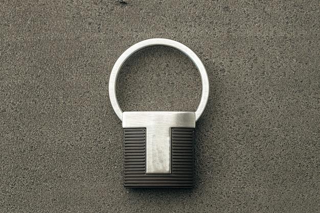 Colgante de llave de metal sobre fondo de hormigón oscuro