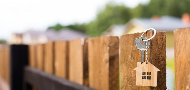 Colgante de madera de una casa y llave en una valla