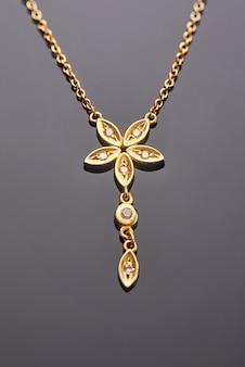 Colgante de oro amarillo con forma de flor de cinco hojas con diamantes.