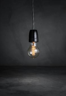 Colgar las bombillas con brillar intensamente en el fondo oscuro del sitio del cemento.