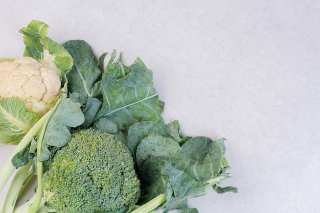 Coliflor y brócoli en mesa blanca.