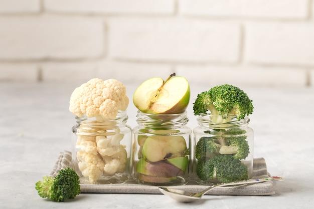 Coliflor, brócoli, rodajas de manzana, en frascos para comida para bebés, en una fila, en una servilleta de tela, cuchara de metal, fondo claro