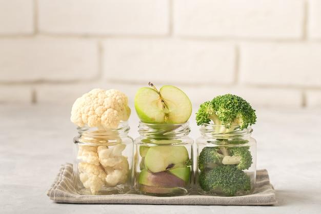 Coliflor, brócoli, rodajas de manzana, en frascos para comida para bebés, en una fila, sobre una servilleta de tela, fondo claro