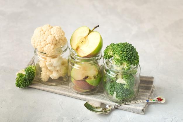 Coliflor, brócoli, rodajas de manzana, en frascos para papilla, de forma idiagonal, sobre una servilleta de tela, cuchara de metal, fondo claro