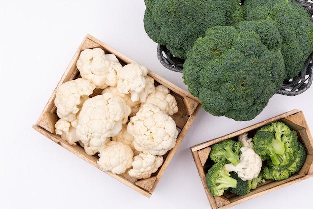 Coliflor en caja cerca del brócoli en la cesta vista superior sobre superficie blanca