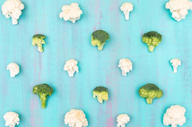 Coliflor fresca y patrón de brócoli en la superficie azul