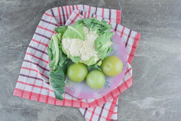 Coliflor fresca con tomates verdes inmaduros.