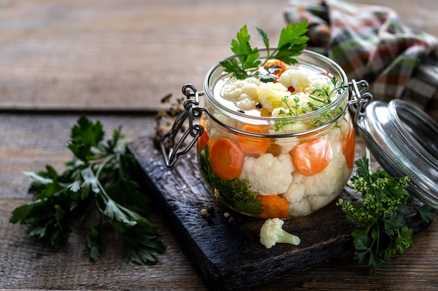 Coliflor en vinagre con zanahorias en un frasco de vidrio sobre una mesa de madera oscura.