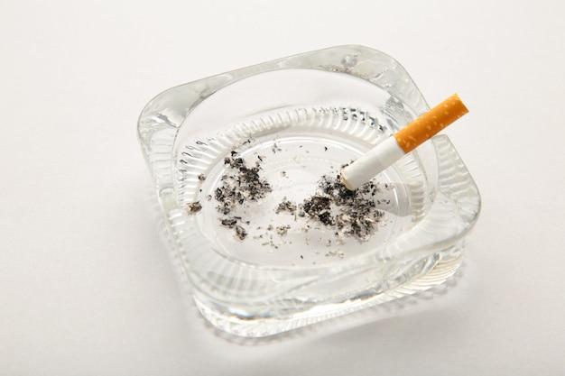 Colilla de cigarrillo con ceniza en cenicero sobre fondo gris
