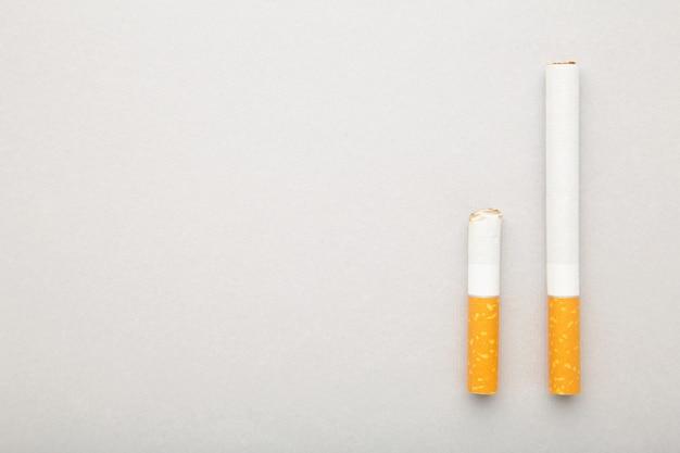 Colilla de cigarrillo con cigarrillo sobre fondo gris