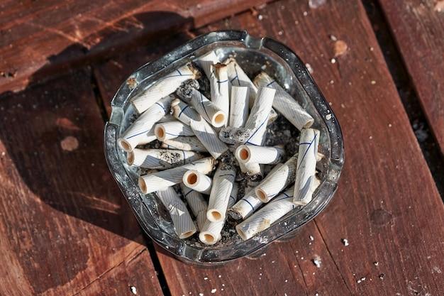 Las colillas de cigarrillos se encuentran en un cenicero sucio de vidrio