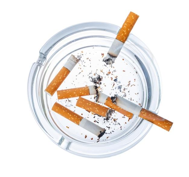 Colillas de cigarrillos quemados en un cenicero aislado sobre fondo blanco.