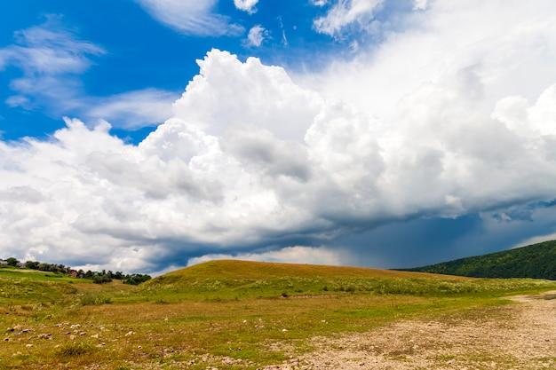 Colina con hierba verde y dramáticas nubes de tormenta en lo alto