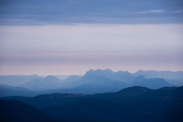 Colinas y montañas cubiertas de niebla en un día sombrío