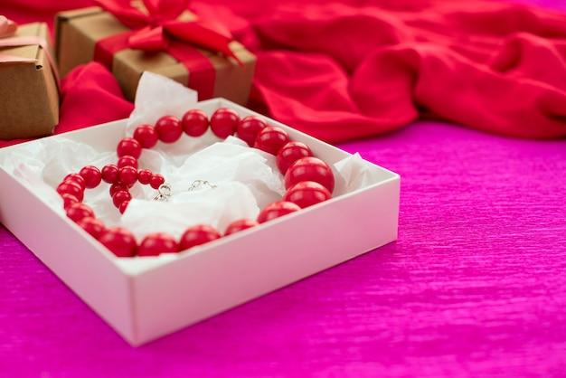 El collar brillante está empacado en una caja blanca sobre un fondo rosa.