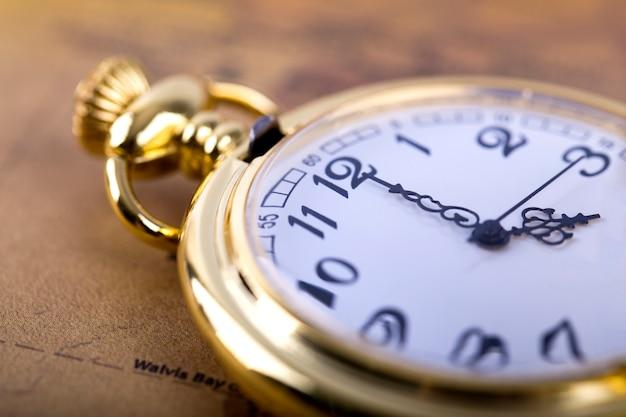 Collar clásico reloj de bolsillo dorado en mapa retro.