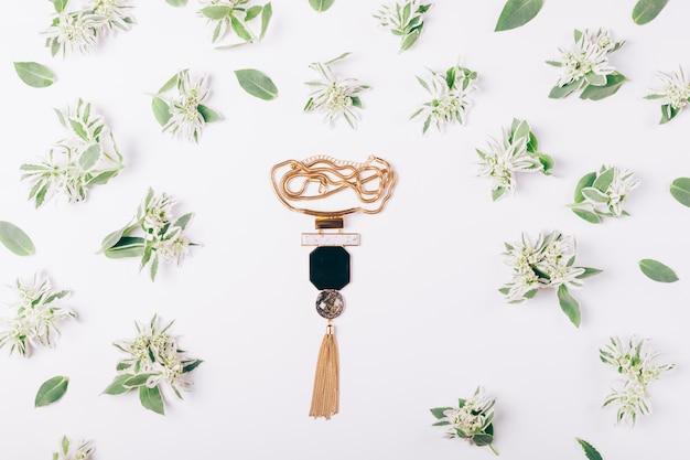 Collar femenino en una mesa blanca entre flores verdes.