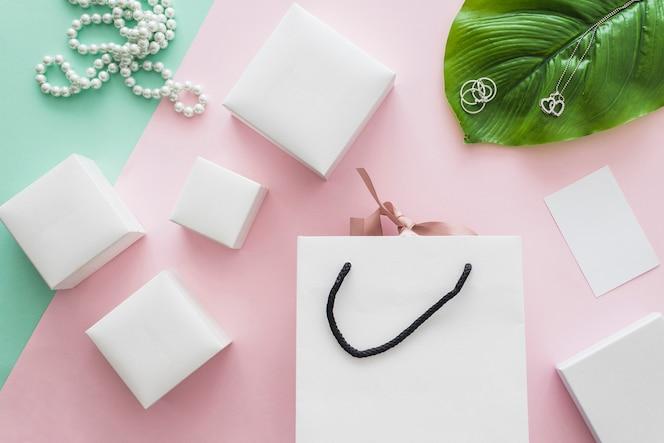 Collar de perlas y muchas cajas blancas con bolsa sobre fondo rosa