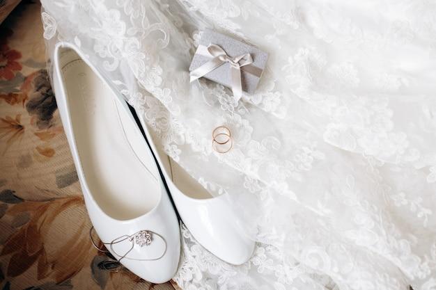 Collar, zapatos blancos y anillos de boda en el vestido de novia.